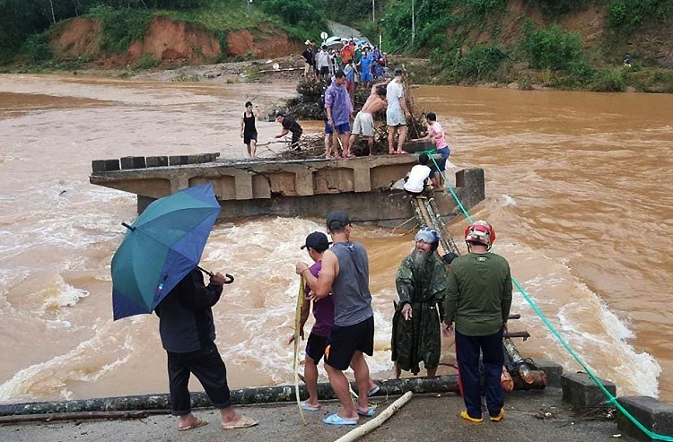 Nhiều người tìm cách qua lòng hồ Đồng Mít bằng cầu tạm từ cây cối. Ảnh: Trọng Lợi.