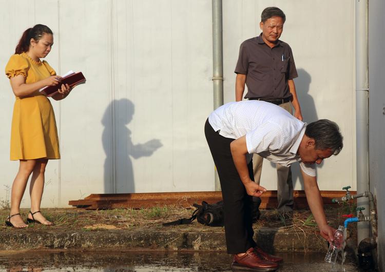 Cán bộ Trung tâm kiểm soát bệnh tật (Sở Y tế Hà Nội) lấy mẫu nước để kiểm tra ngày 11/10. Ảnh: Võ Hải.