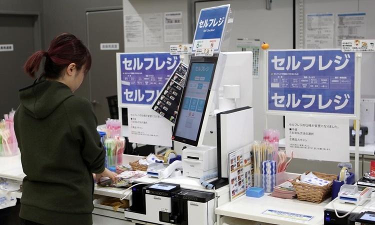 Người mua hàng thanh toán bằng điện thoại di động tại máy tính tiền tự động ở một cửa hàng tiện lợi tại Tokyo, Nhật Bản. Ảnh: Reuters.