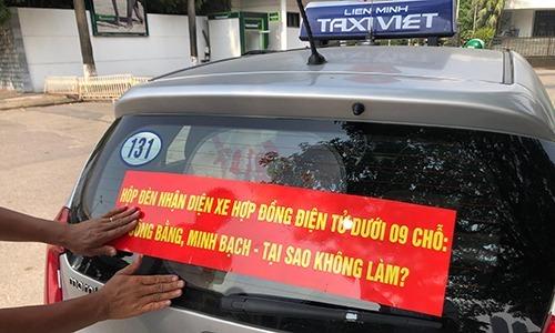 Nhiềuhãng taxi truyền thống tại Hà Nộidán khẩu hiệu yêu cầu taxi công nghệ gắn mào. Ảnh:Anh Tú