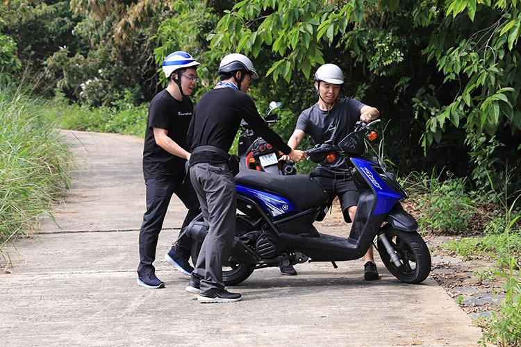Một nhóm du khách Trung Quốc phải quay đầu xe tay ga đi về khi cố leo dốc tại đoạn đường bê tông từ đỉnh Bàn Cờ về Bãi Bắc. Ảnh: Nguyễn Đông.
