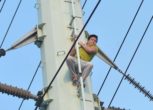 Nam thanh niên leo lên cột điện cao thế trên đường Tố Hữu và cố thủ suốt 3 giờ đồng hồ. ảnh: Tất Định