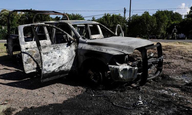 Xe cảnh sát cháy xém sau vụ đột kích của băng đảng tại làng El Aguaje, bang Michoacan, Mexico hôm 14/10. Ảnh: Reuters.