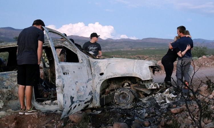 Thành viên gia đình các nạn nhân bên chiếc xe bị những tay súng, nghi là băng đảng, Mexico bắn cháy. Ảnh: Reuters.