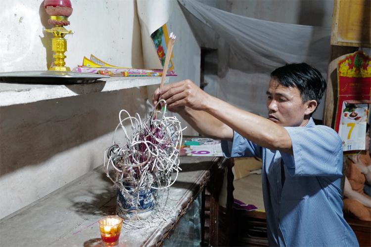 Nguyễn Thọ Hạnh, anh trai của Nguyễn Thọ Tuân, thắp hương trước bàn thờ tổ tiên tại nhà ở xã Nam Thành, Yên Thành, Nghệ An mong mọi việc diễn ra suôn sẻ. Ảnh: Ngọc Thành