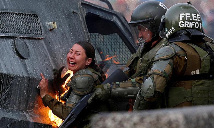 Một nữ cảnh sátSantiago đau đớn vì trúng bom xăng hôm 4/11. Ảnh: Reuters.