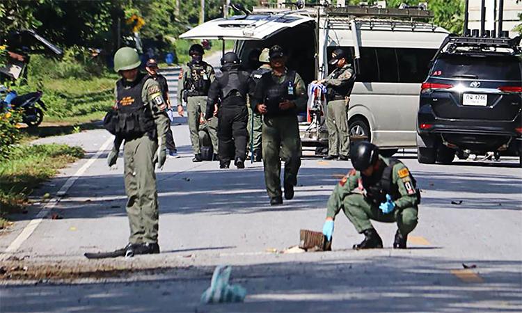 Chuyên gia bom mìn Thái Lan kiểm tra khu vực quanh trạm gác xảy ra vụ nổ súng khiến nhiều người chết hôm 6/11. Ảnh: AFP.