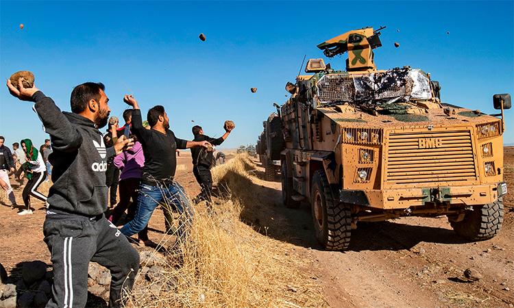 Dân làng người Kurd ném đá vào thiết giáp Thổ Nhĩ Kỳ tuần tra chung với cảnh sát quân sự Nga gần thị trấn al-Maabadah, Syria ngày 8/11. Ảnh: AFP.