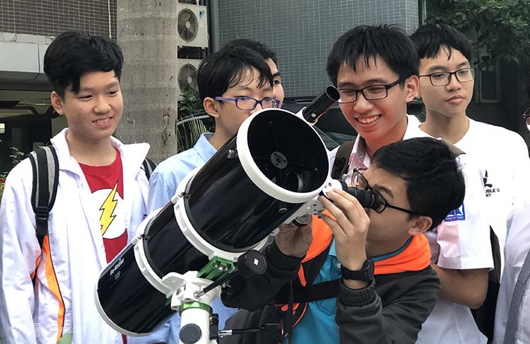 Các bạn trẻ hào hứng trải nghiệm với kính thiên văn.