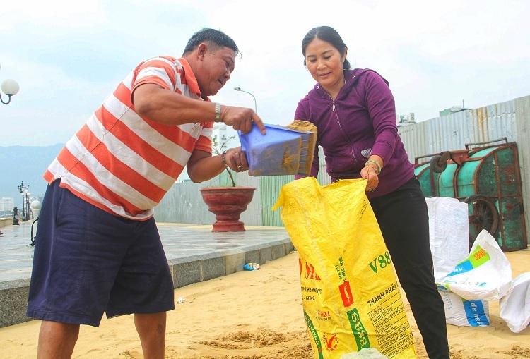 Người dân TP Quy Nhơn dồn cát vào bao để chằng chống nhà trước khi bão Nakri đổ bộ. Ảnh: Thạch Thảo.