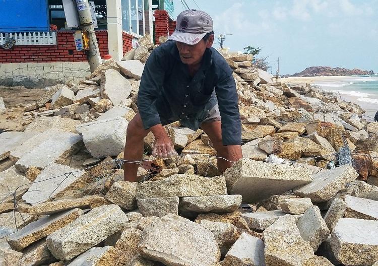 Người dân dùng lưới thép bao quanh các tảng đá để gia cố kè biển xã Nhơn Hải. Ảnh: Thạch Thảo.