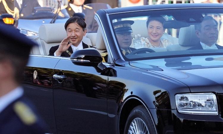 Nhật hoàng Naruhito và Hoàng hậu Masako diễu hành trên chiếc xe mui trần, đi qua đường phố ở trung tâm thủ đô Tokyo ngày 10/11. Ảnh: AP.