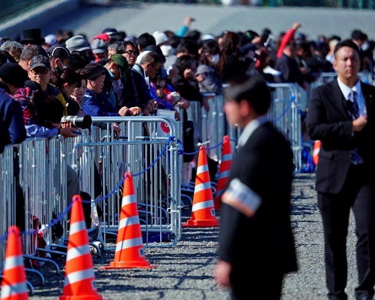 Người dân tập trung bên đường chờ đoàn xe của Nhật hoàng đi qua. Ảnh: AP.