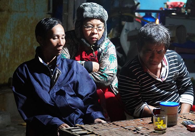 Gia đình ông Nguyễn Đúng theo dõi diễn biến bão qua điện thoại. Ảnh: Việt Quốc.