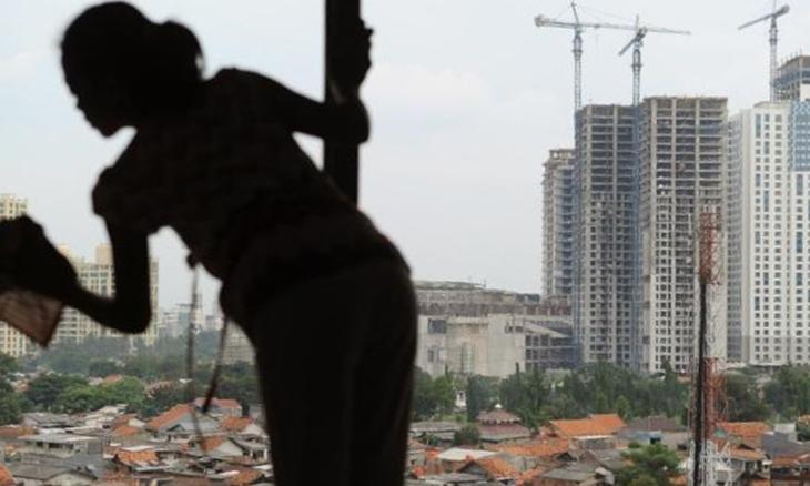 Một cô giúp việc lau cửa sổ căn hộ tại Jakarta. Ảnh: AFP.