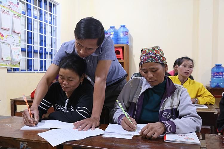 Thầy giáo bắt tay tập viết cho một học viên vừa tham gia lớp học.Ảnh:Hoàng Táo