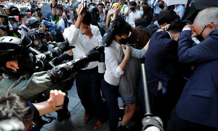 Cảnh sát Hong Kong dùng bình xịt hơi cay để giải tán đám đông biểu tình ở quận Central hôm nay. Ảnh: Reuters.