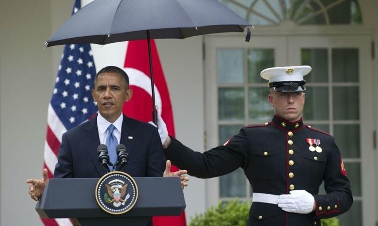 Một lính thủy đánh bộ Mỹ che ô cho tổng thống Barack Obama khi ông phát biểu tại Nhà Trắng hồi năm 2015. Ảnh: AFP.