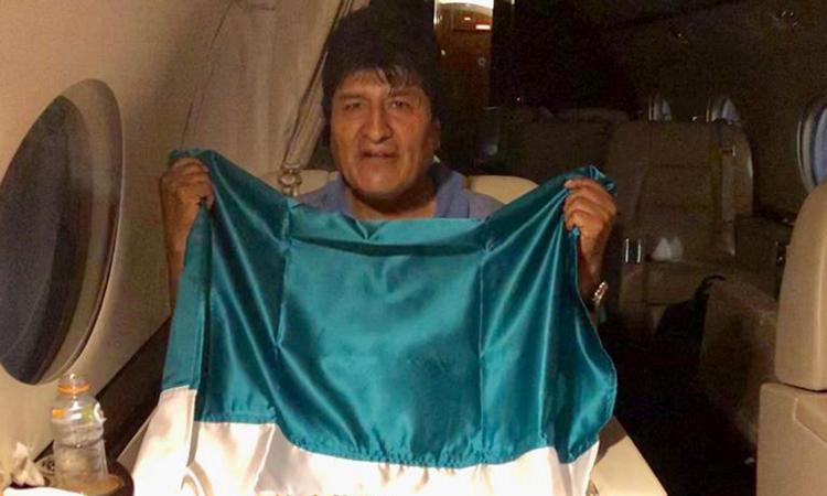 Cựu tổng thống Morales cầm lá cờ Mexico và ngồi trên máy bay của chính phủ Mexico tại một địa điểm chưa xác định hôm 11/11. Ảnh: Reuters.