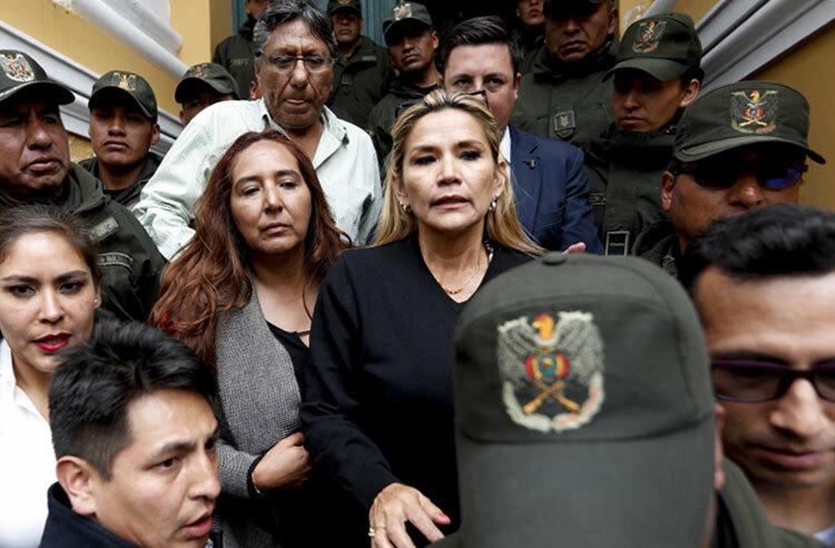 Bà Anez (áo đen, giữa) được các binh sĩ hộ tống tại thủ đô La Paz hôm 11/11. Ảnh: AP.