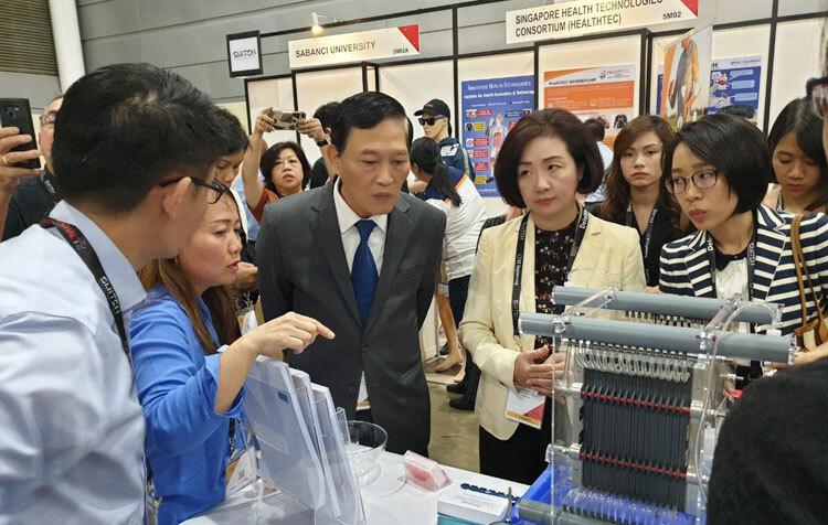 Thứ trưởng Trần Văn Tùng (giữa) và các đại biểu tham quan gian hàng.
