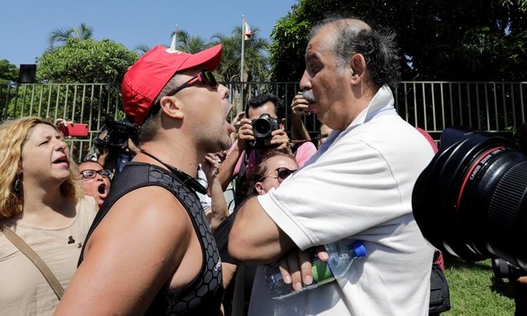 Người ủng hộ Maduro và Guaido cãi nhau ở bên ngoài sứ quán Venezuela tại Brazil ngày 13/11. Ảnh: Reuters.