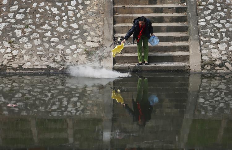 Một người dân vứt rác xuống sông Tô Lịch đoạn chảy qua Khương Trung. Ảnh: Ngọc Thành.
