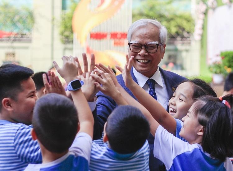Thầy Nguyễn Văn Hòa high-five với học sinh ở sân trường. Ảnh: Dương Tâm