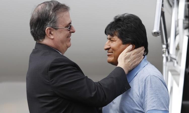 Ngoại trưởng Mexico Marcelo Ebrard (trái) chào đón cựu tổng thống Bolivia Evo Morales tại sân bay ở thủ đô Mexico City ngày 12/11. Ảnh: AP.