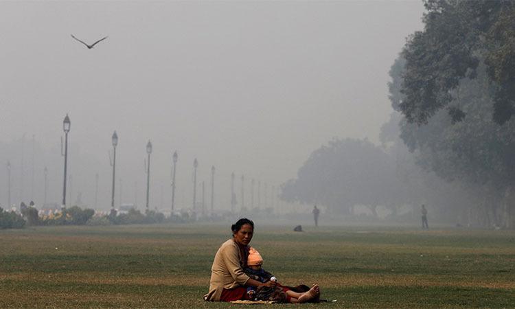 Một phụ nữ và trẻ em trong công viên cạnh Đài tưởng niệm India Gate ở thủ đô New Delhi, Ấn Độ ngày 13/11. Ảnh: Reuters.