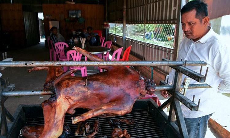 Người đàn ông bên quầy thịt chó nướngở tỉnh Kampong Cham, Campuchia ngày 26/10. Ảnh: AFP.