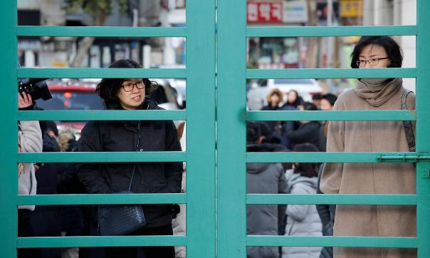 Phụ huynh chờ con thi đại học ở Seoul hôm nay. Ảnh: Reuters