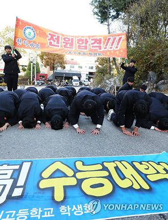 Một nhóm học sinh trung học gập đầu trước trườngTaejang ở thành phốSuwon để chúc các anh chị khóa trên hoàn thành tốt kỳ thi đại học. Ảnh: Yonhap