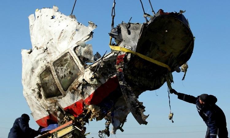 Công nhân vận chuyển mảnh vỡ của máy bay MH17 ở miền đông Ukraine tháng 7/2014. Ảnh: Reuters.
