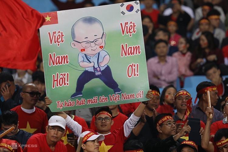 CĐV Việt Nam trưng tấm bảng vẽ hình cách điệu Park Hang-seo trước trận đấu với UAE hôm qua ở Mỹ Đình.
