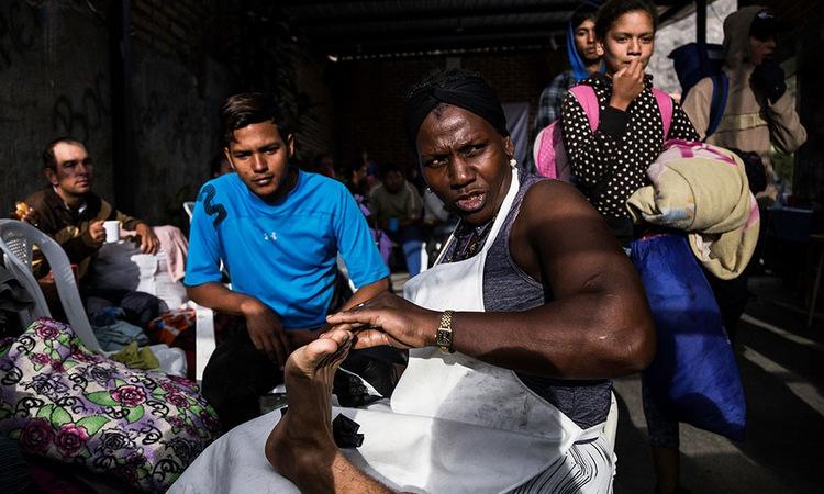 Carcelen (đeo tạp dề) giúp điều trị vết rộp dưới chân một người di cư. Ảnh: Al Jazeera.
