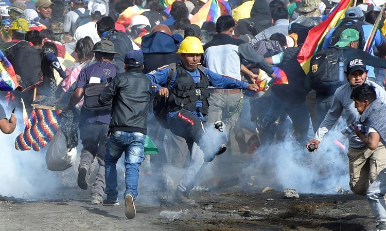 Những nông dân ủng hộ Morales đối phó với hơi cay của lực lượng an ninh ở ngoại ô thành phố Cochabamba, Bolivia hôm 15/11. Ảnh: Reuters.