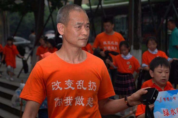 Ông Zhong Congrong cầm máy ghi âm phát thông điệp kêu gọi mọi người không xả rác. Ảnh: SCMP
