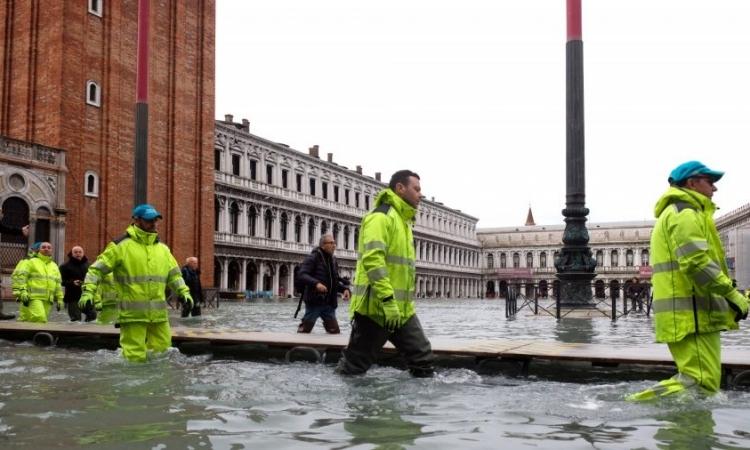Công nhân dọn dẹp Quảng trường San Marco, Venice, Italy, sau khi nước lũ tiếp tục tấn công hôm 17/11. Reuters.