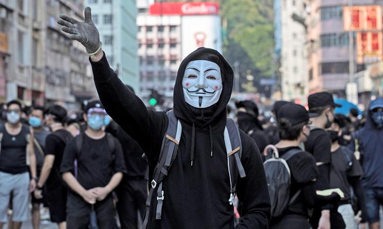 Người biểu tình Hong Kong đeo mặt nạ tuần hành trên phố hôm 1/10. Ảnh: Reuters.