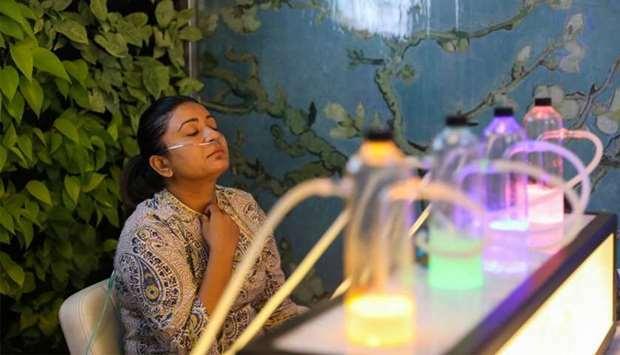 Một khách hàng sử dụng dịch vụ khí oxy sạch tại quán bar Oxy Pure. Ảnh: Gulf Times