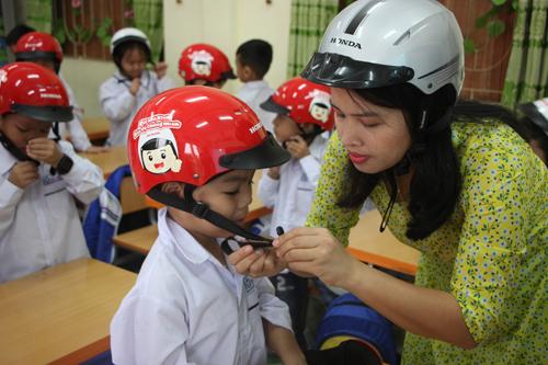 2. Cô giáo hướng dẫn các em học sinh đội mũ đúng cách  (2)