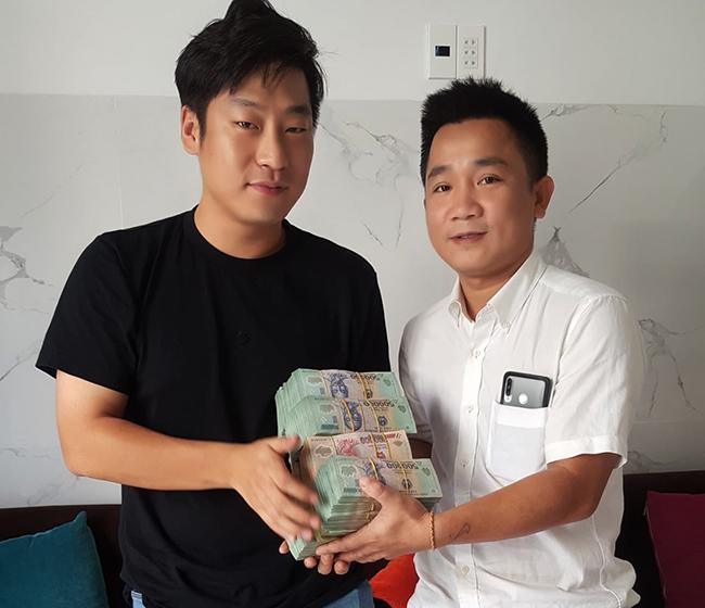 [Bùi QuốcTuấn đưa lại số tiền cho anh Seol Young Jin, du khách Hàn Quốc. Ảnh: Đại Hiệp.