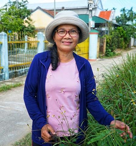 Bà Bùi Thị Phong, 65 tuổi, trên con đường được xây từ tiền phúng điếu của cha mẹ. Ảnh: Phạm Linh.