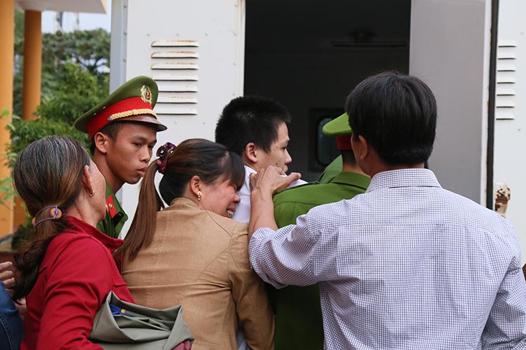 Người nhà ôm khóc khi các bị cáo bị dẫn ra xe. Ảnh: Hoàng Táo