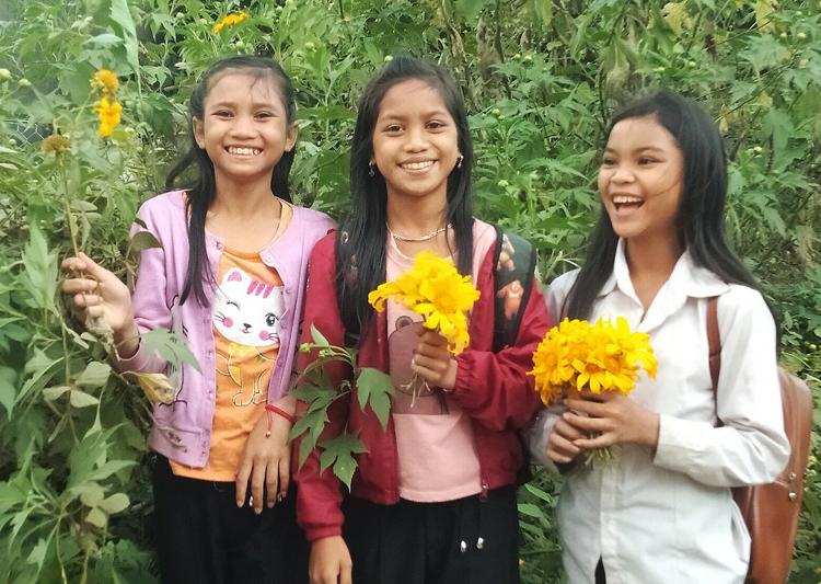 Nhóm học sinh trường THCS Đăk Rơ Ông hái hoa giã quỳ bên đường, tặng thầy cô. Ảnh: Ngọc Oanh.