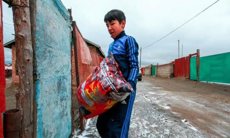 Một cậu bé ở Ulaanbaatar bêtúi than không khóisau khi vừa mua ngày 19/10. Ảnh: AFP.