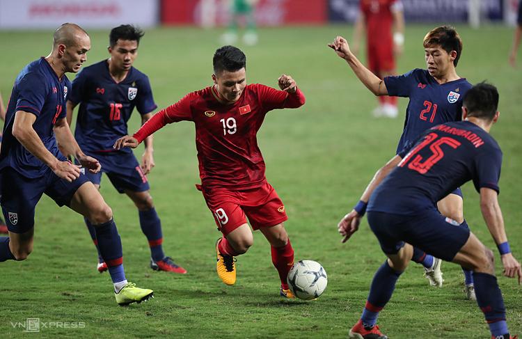 Quang Hải đi bóng trong sự đeo bám của các cầu thủ Thái Lan, trên sân Mỹ Đình tối 19/11. Ảnh: Đức Đồng.