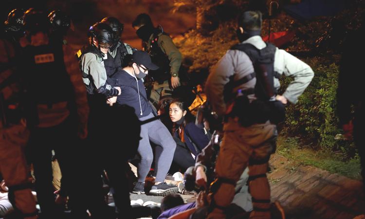 Những người biểu tình bị cảnh sát bắt khi tìm cách rời PolyU tối 19/11. Ảnh: Reuters.