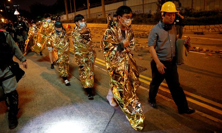 Người biểu tình đầu hàng cảnh sát xếp hàng chờ được đưa tới bệnh viện tối 19/11. Ảnh: Reuters.